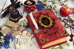Red witch book with runes, mystic objects and cup of tea on wooden table. Occult, esoteric and divination still life. Halloween background with vintage objects stock image
