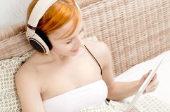 Red woman in bed listening to the music Royalty Free Stock Photos