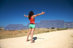 Red woman greeting solar panels Stock Photos