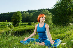 Red woman practicing fitness yoga outdoors Stock Images