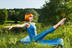 Red woman practicing fitness yoga outdoors Royalty Free Stock Image