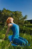 Red woman practicing fitness yoga outdoors Stock Photography