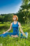 Red woman practicing fitness yoga outdoors Stock Image