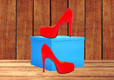 Red woman shoe and blue gift box on wooden table Stock Images
