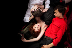 Red woman and two men - decadence style. Red woman and two men love triangle - decadence style Stock Photo