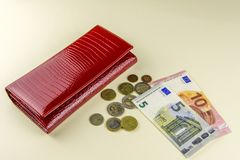 Red woman wallet. Banknotes ten and five euros. A few coins. Beige background. stock photos