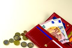 Red woman wallet. Banknotes ten and five euros. A few coins. Beige background. stock photo