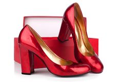 Red women`s high-heeled shoes patent leather and red box on a white background  close up royalty free stock images