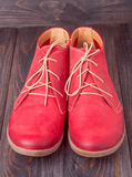 Red women's leather shoes with laces on  wooden background Royalty Free Stock Photo
