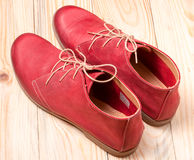 Red women's leather shoes with laces on  wooden background Stock Photos