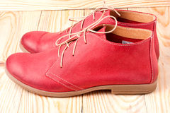 Red women's leather shoes with laces on  wooden background Royalty Free Stock Photos