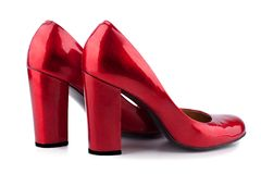 Red women`s shoes with high heels made of lacquered leather side view on a white background  close up stock photos