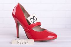 Red women`s shoes by March 8. Heeled shoes and wooden calendar. Design a lovely gift royalty free stock image