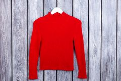 Red women`s woolen pullover, flat lay. Top view. Grey desk surface background Stock Image