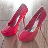 Red women shoes on wooden background. Royalty Free Stock Image