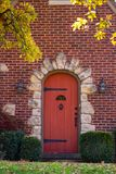 Red wood arched door surrounded by a rock frame in a brick house with castle like hardware with fall leaves hanging down on an aut royalty free stock photo