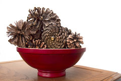 Red Wood bowl filled with large Pinecones Stock Photo