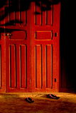 Red wood door and slippers Stock Images