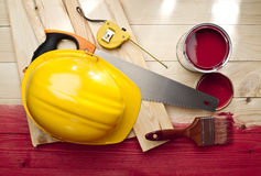 Red wood floor with a brush, paint, saw and helmet stock image