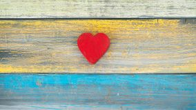 A single red heart on a wood background. A red wood heart shape sits in the center of this blue, yellow and green wood plank background Royalty Free Stock Photography