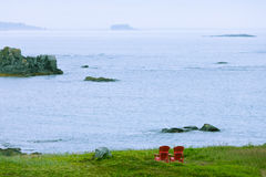 Relaxing at Strait of Belle Isle coast NL Canada. Red wooden Adirondack Chairs in beautiful coastal landscape of Strait of Belle Isle, Newfoundland, NL, Canada stock photos