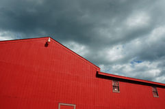 Red wooden barn exterior. Exterior of red wooden barn in New England with storm clouds overhead Royalty Free Stock Photography