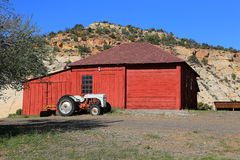 Red wooden barn and tractor. Royalty Free Stock Photos