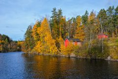 Red wooden barn. Traditional red wooden barn on the lake on a sunny autumn day Royalty Free Stock Photo