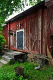 Red wooden barn. Traditional red wooden barn with some hand tools at rainy day. Tammisaari, Finland Royalty Free Stock Photography