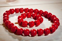 Red wooden beads and bracelet on a wooden background Royalty Free Stock Photo