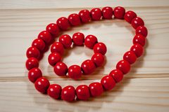 Red wooden beads and bracelet on a wooden background Royalty Free Stock Images