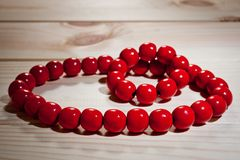 Red wooden beads and bracelet on a wooden background Stock Image