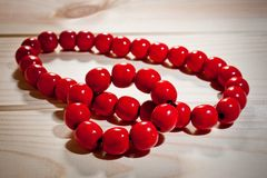 Red wooden beads and bracelet on a wooden background Royalty Free Stock Photos