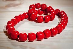 Red wooden beads and bracelet on a wooden background Stock Photo