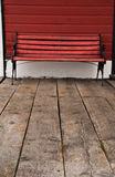 Red wooden bench. A bench of red painted wood and black iron stands behind an aged wooden floor and painted red exterior wall at an old railway station royalty free stock photos