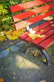 Red, wooden bench in the park in Autumn. Poland Stock Photo