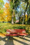 Red, wooden bench in the park in Autumn. Poland Stock Photos
