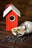 Red wooden bird house with seed Royalty Free Stock Images