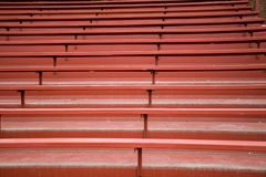 EMPTY RED WOODEN BLEACHERS. Red wooden bleachers wait for the fans to come and cheer on their team royalty free stock images