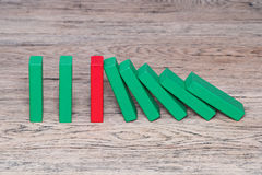 Red wooden block preventing domino effect Stock Images