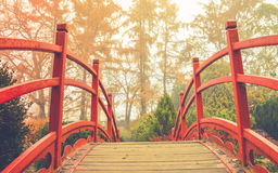 Red wooden bridge in soft light. Wooden bridge with the red handrails in a japanese garden, against a background of autumnal trees royalty free stock images