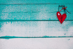 Red wooden broken heart hanging on sandy turquoise sign