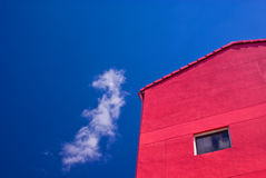 Red wooden building. Exterior of red wooden building with blue sky and cloudscape background Stock Photography