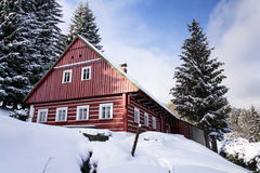 Red wooden cabin in a frosty snowy country Stock Images