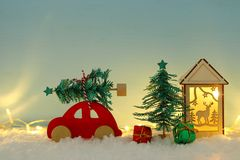 Red wooden car carrying a christmas tree over snow in front of blue background and golden garland lights. Red wooden car carrying a christmas tree over snow in royalty free stock photo
