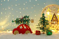 Red wooden car carrying a christmas tree over snow in front of blue background and golden garland lights. stock photo