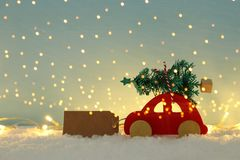 Red wooden car carrying a christmas tree over snow in front of blue background and golden garland lights. royalty free stock photos
