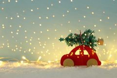 Red wooden car carrying a christmas tree over snow in front of blue background and golden garland lights. Red wooden car carrying a christmas tree over snow in royalty free stock photos