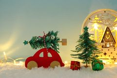 Red wooden car carrying a christmas tree over snow in front of blue background and golden garland lights. Red wooden car carrying a christmas tree over snow in royalty free stock images