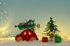 Red wooden car carrying a christmas tree over snow in front of blue background and golden garland lights. Red wooden car carrying a christmas tree over snow in royalty free stock image